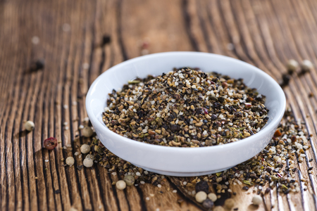 peppercorns: Small bowl with crushed Peppercorns on vintage wooden background Stock Photo
