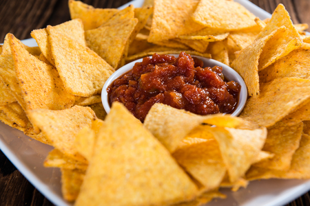 nachos: Nachos with Salsa Sauce (close-up shot) on wooden background Stock Photo
