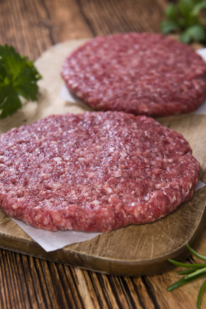 minced beef: A raw Burger (minced Beef) on dark wooden background