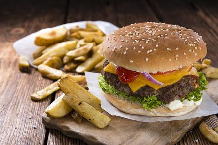 carne asada: Hamburguesa de carne de vaca hecho en casa con queso y patatas fritas en el fondo de madera Foto de archivo