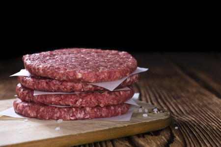 A raw Burger (minced Beef) on dark wooden background