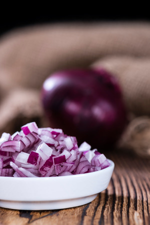 red onions: Portion of diced Red Onions (close-up shot) on an old rustic wooden table