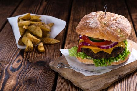 hamburguesa: Hamburguesa Ciabatta con patatas fritas hechas en casa en el fondo rústico