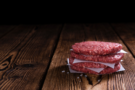 minced beef: Some fresh made Burgers (raw minced Beef) on an old wooden table Stock Photo