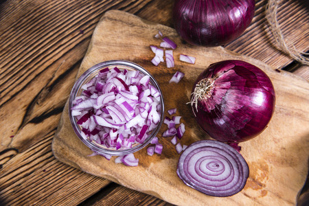Small bowl with (diced) Red Onions on wooden background
