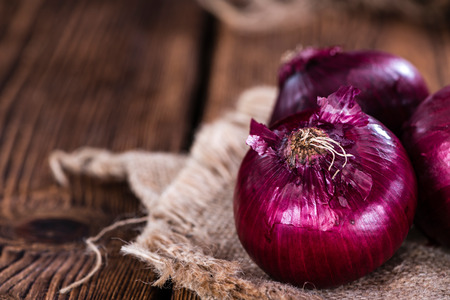 red onions: Some fresh Red Onions (close-up shot) on an wooden table