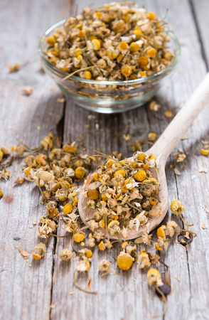 chamomilla: Portion of dried Camomile (close-up shot) on an old wooden table