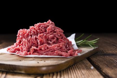 Gehakt vlees (rundvlees) als gedetailleerde close-up shot op donkere houten achtergrond