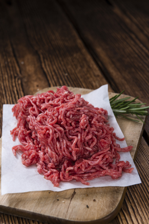 Minced Meat (Beef) as detailed close-up shot on dark wooden background