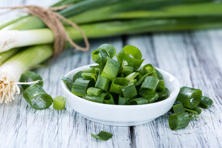 scallions: Bowl with fresh sliced Scallions (close-up shot) on wooden background