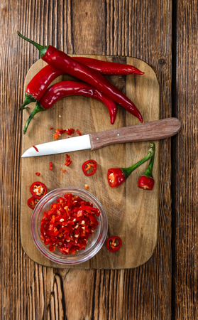 red: Cutted red Chilis in a bowl (close-up shot) on wooden background Stock Photo
