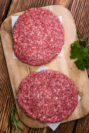 mincemeat: Some fresh made Burgers (raw minced Beef) on an old wooden table Stock Photo
