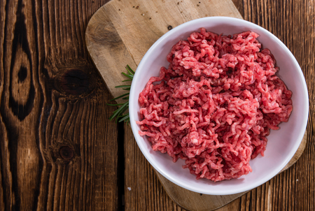 Portion of Minced Meat on an old wooden table (close-up shot)