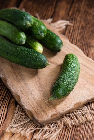 marinated gherkins: Small Cucumbers (close-up shot) on vintage wooden background