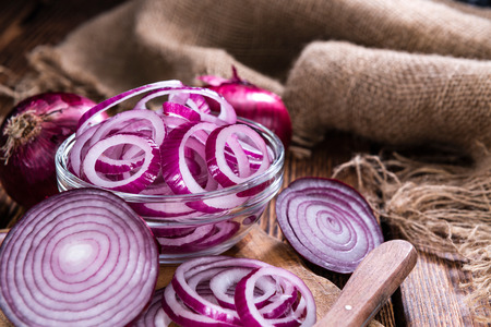 red onion: Peque�o recipiente con anillos de cebolla roja (close-up shot) sobre fondo de madera r�stica