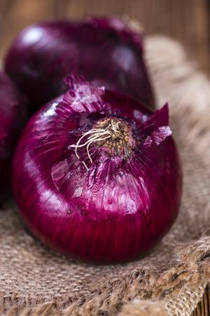onion: Las cebollas rojas (primer plano tiro) en una vieja mesa de madera r�stica