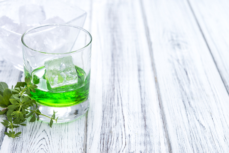 sweet woodruff: Woodruff Liqueur in a small glass (on wooden background) Stock Photo