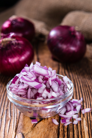 cubed: Some fresh Red Onions (diced) on an old wooden table