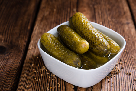 Preserved Gherkins (on wooden background) as detailed close-up shot