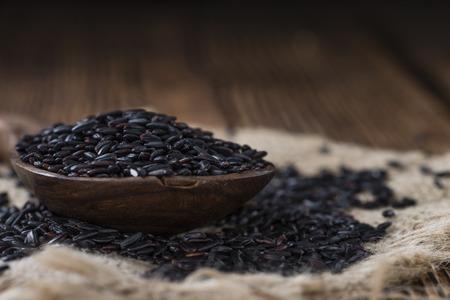black rice: Portion of Black Rice (close-up shot) on wooden background