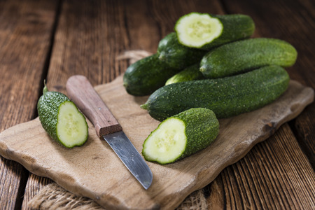 gherkins: Small green Gherkins (detailed close-up shot) on wooden background Stock Photo