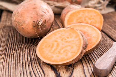 sweet: Raw Sweet Potato (detailed close-up shot) on wooden background Stock Photo