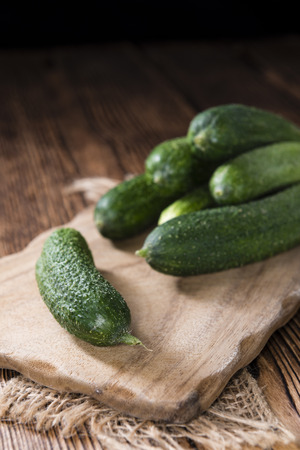 marinated gherkins: Small green Gherkins (detailed close-up shot) on wooden background Stock Photo