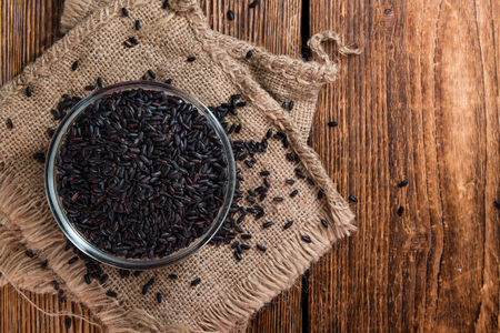 Heap of Black Rice (close-up shot) on an old wooden table