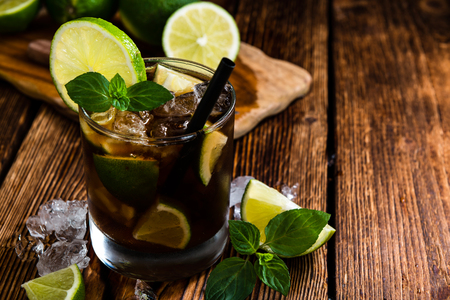 crushed ice: Homemade Cuba Libre with fresh lime, brown rum and crushed ice on an old wooden table