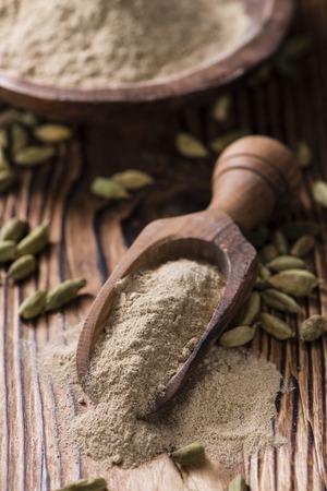 cardamon: Portion of Cardamon Powder (close-up shot) on wooden background
