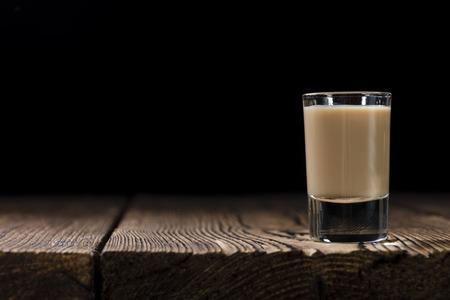 shot: Irish Cream Liqueur (detailed close-up shot) on wooden background