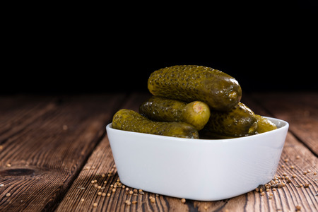 marinated gherkins: Preserved Gherkins (on wooden background) as detailed close-up shot