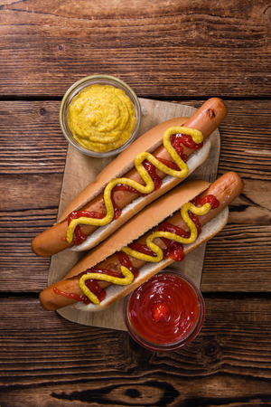 Homemade Hot Dog with ketchup and mustard on rustic wooden background Imagens