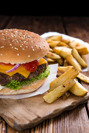 burger: Big Burger with homemade French Fries on rustic wooden background