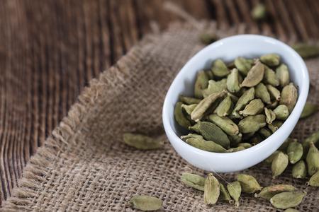 cardamon: Cardamon (seeds) as close-up shot on vintage wooden background Stock Photo