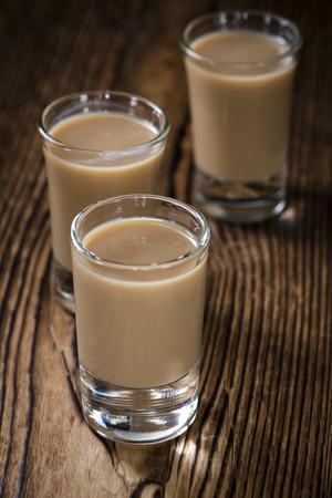 liqueur: Glass with cold Cream Liqueur on vintage wooden background