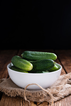 marinated gherkins: Some small Cucumbers (close-up shot) on vintage wooden background