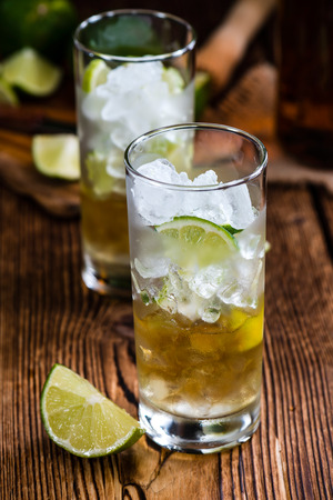 longdrink: Rum on the rocks (for a Cuba Libre longdrink)  on wooden background