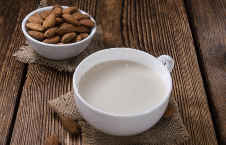 mleko: Tasty Almond Milk (selective focus) on vintage wooden background