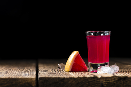 shot glass: Shot Glass with Grapefruit Liqueur on rustic wooden background Stock Photo