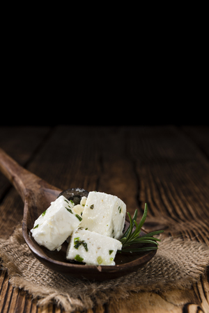 milk products: Greek Feta Cheese on rustic wooden background (close-up shot)