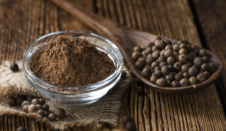 allspice: Old wooden table with Allspice powder (detailed close-up shot)