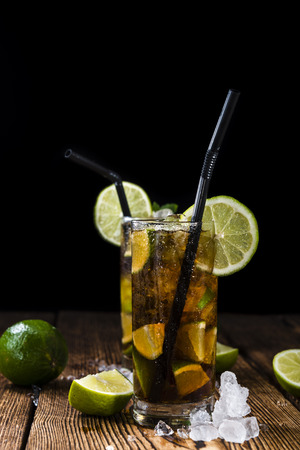 crushed ice: Cuba Libre longdrink with pieces of fresh lime and crushed ice on wooden background