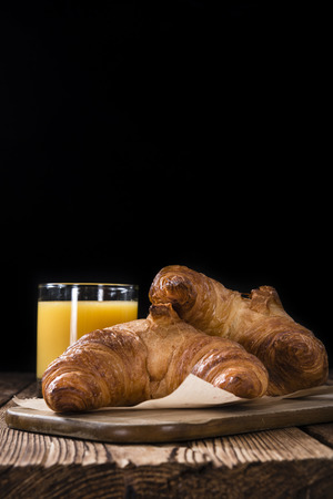 traditionally french: Fresh baked Croissants (close-up shot) on wooden background