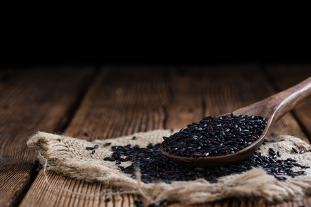 Portion of Black Rice (close-up shot) on wooden background