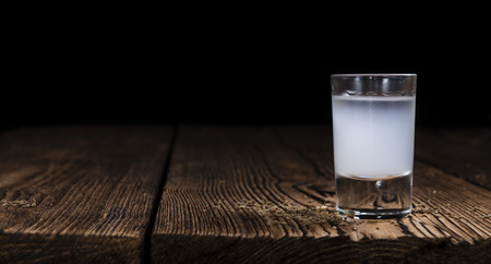 Ouzo (Greek aperitif) in a shot glass on wooden background (selective focus) Archivio Fotografico