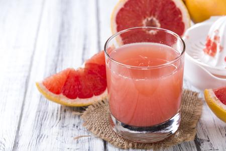 grapefruit juice: Pure Grapefruit Juice (close-up shot) on rustic wooden background