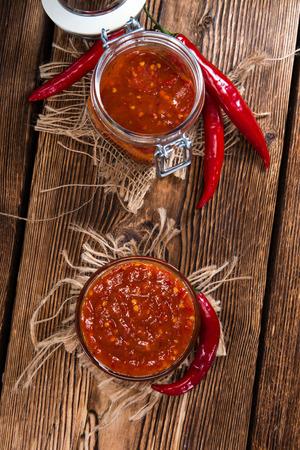 sambal: Portion of Chili Sauce (Sambal Oelek) on rustic wood Stock Photo