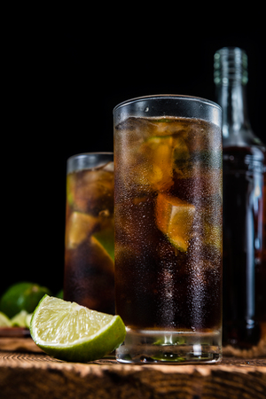 ice crushed: Homemade Cuba Libre with fresh lime, brown rum and crushed ice on an old wooden table