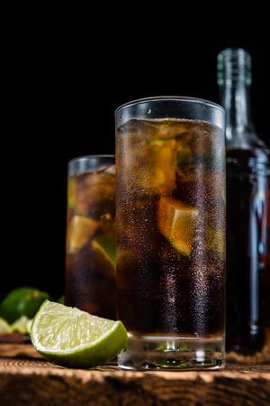 ice crushed: Zelfgemaakte Cuba Libre met verse limoen, bruine rum en gemalen ijs op een oude houten tafel Stockfoto